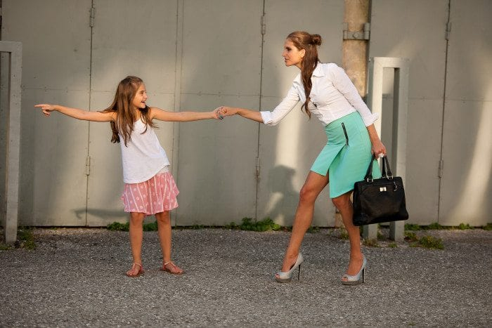 Little girl is pointing at the direction she wants her mom to go, while pulling her mother's hand