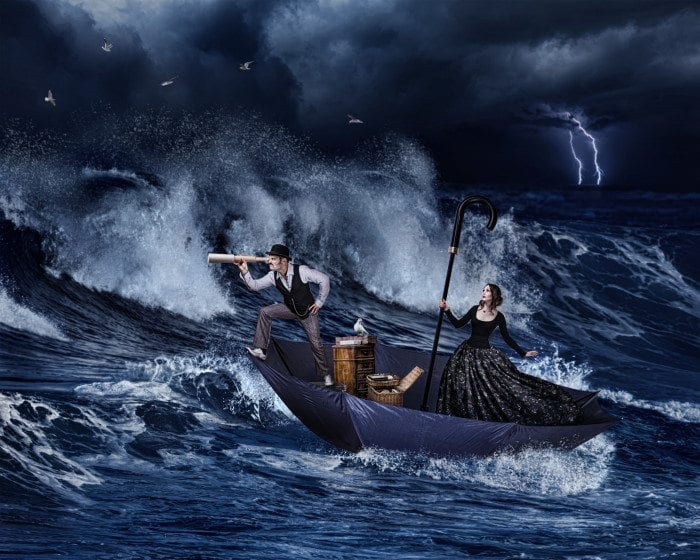 A man is navigating the sea on a giant umbrella with a woman.