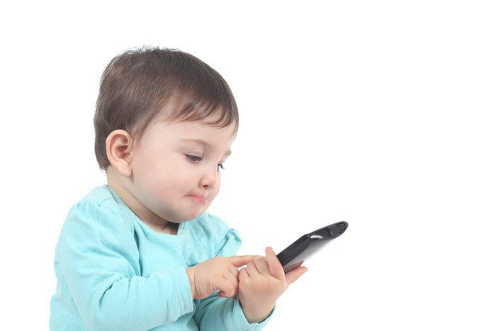 A baby uses a smartphone like an adult.