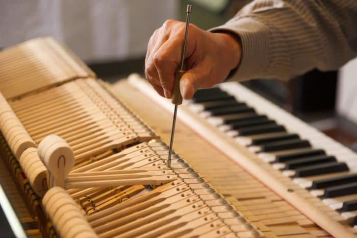 a man is tuning a piano
