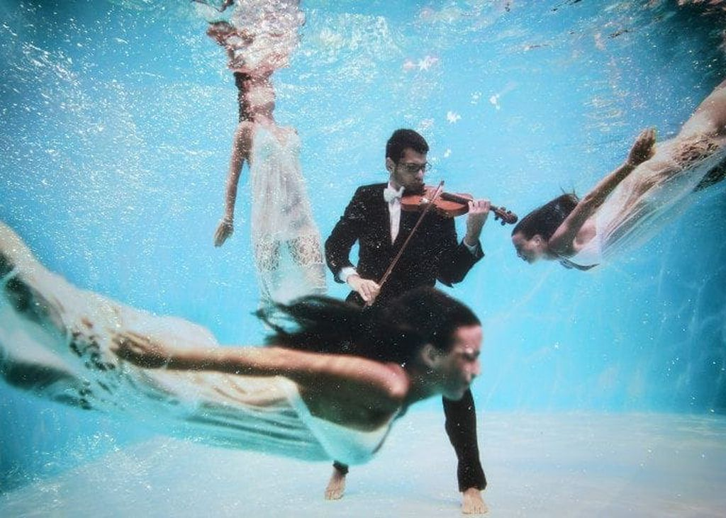Violinist plays the violin under water with girls