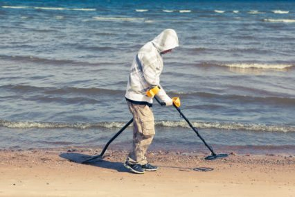 a man is using a metal detector at the beach