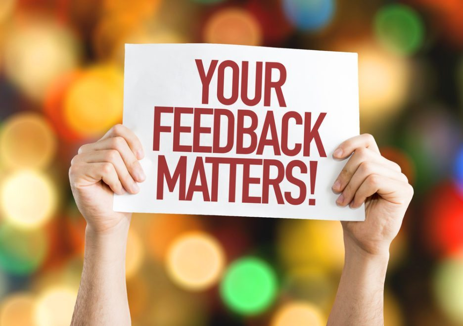 "a person holding a piece of paper which says ""your feedback matters!""."