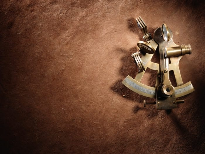 an image of a sextant against a brown background