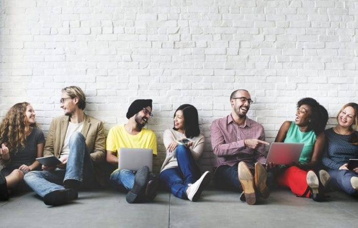 young people sit leaning against a wall and using laptop