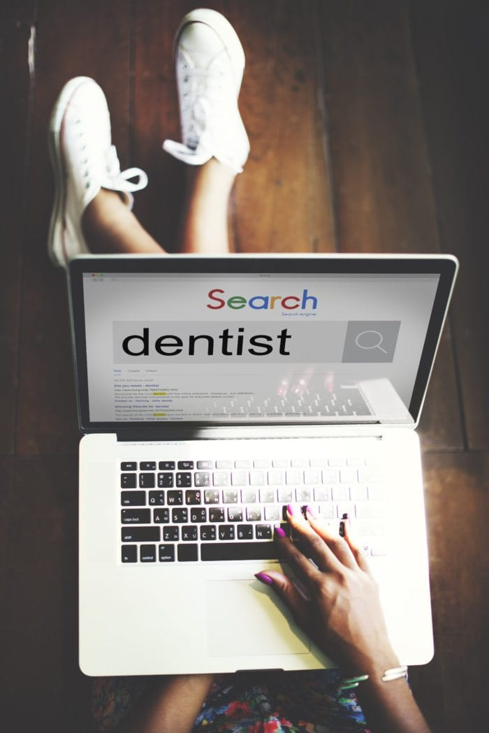 "a person is googling ""dentist"" on her laptop."
