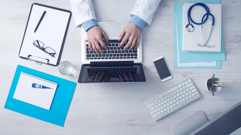 Hands typing on a laptop with, doctor products on the desk. important to understand doctors to create their website.