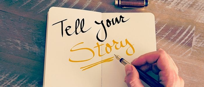 "Hand writing ""tell your story"" in a book"