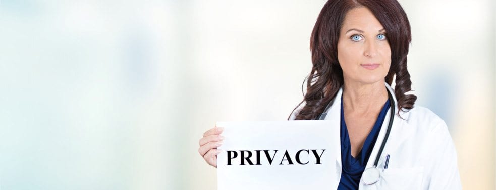 a female doctor holding the sign that says privacy