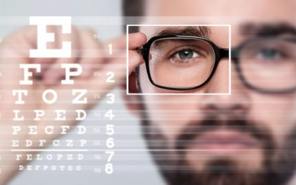 Guy holding glasses with focus on right eye