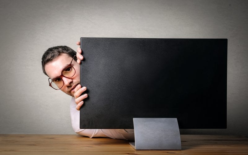 Man hiding behind screen