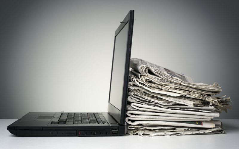 Laptop with pile of newspapers piled behind the screen
