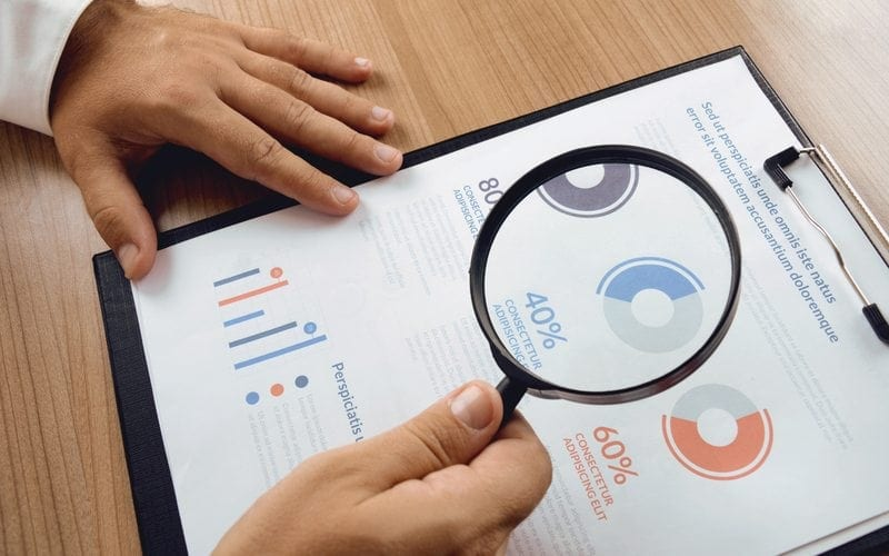 Market research. Businessman hand holding magnifier and closer study report from market research.