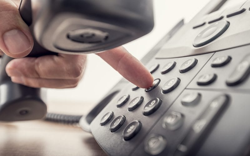 Person holding a telephone receiver and dialing a number