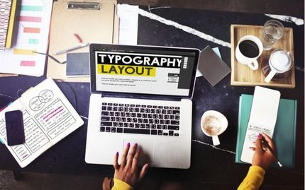 """Design Professional at laptop computer with wording """"typography layout"""""""