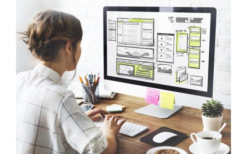 Designer at her computer planning out a website layout for her Medical Website Design