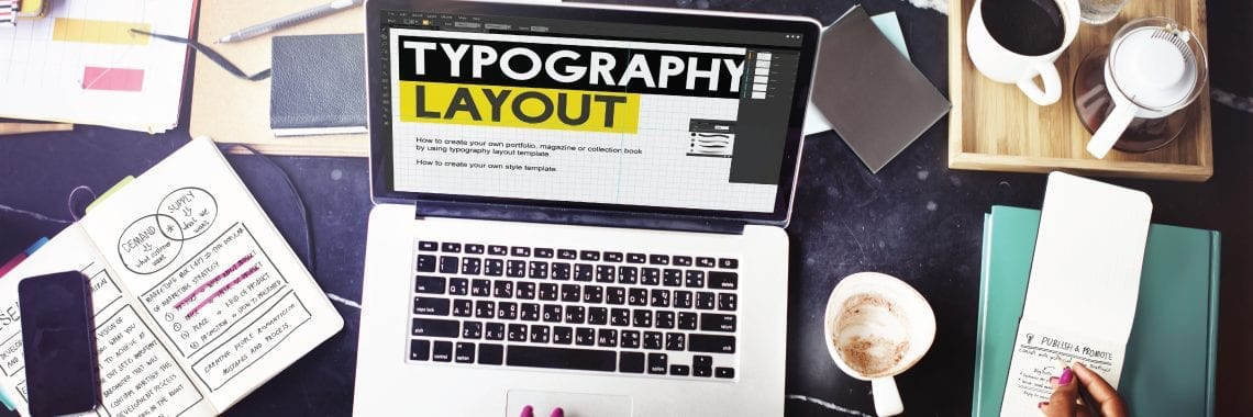 "Design Professional at laptop computer with wording ""typography layout"""