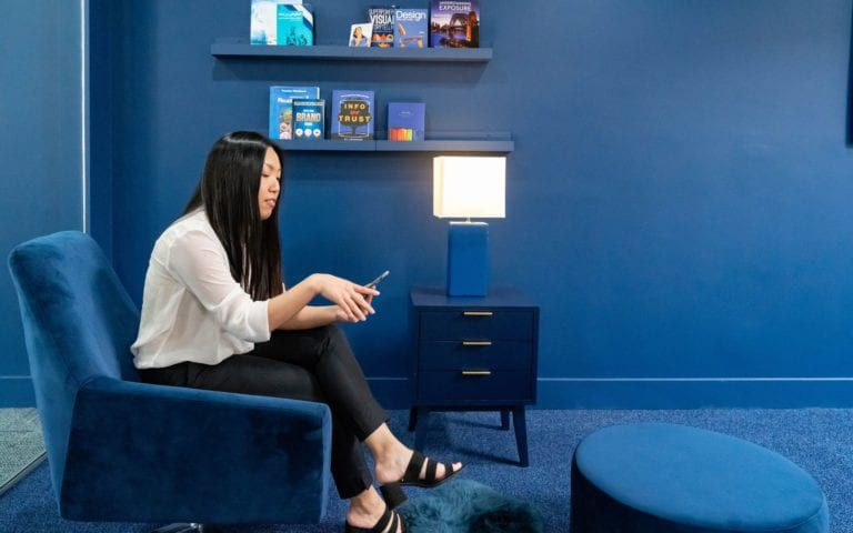 Belinda Tran the VP of O360 sitting on a blue chair in the blue area of the O360 HQ